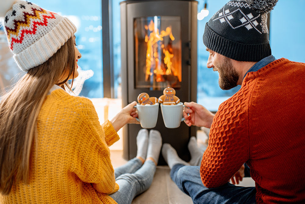 Toasting hot chocolate in front of fireplace